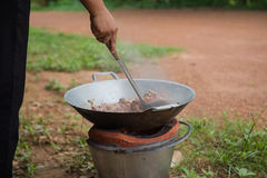 Cooking with pan and charcoal stove Royalty Free Stock Photos