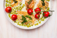 Cooking pan with chicken breast , green pea and roast tomatoes in cream sauce on wooden background, top view Royalty Free Stock Photos