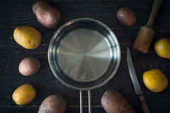 Cooking pan surrounded by raw potatoes on the wooden table horizontal. Cooking pan surrounded by raw potatoes on the wooden table top view horizontal Royalty Free Stock Photography