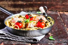 Cooking pan with traditional italian pasta spaghetti with roasted cherry tomatoes, capers and bacon with mint on a wooden table, s. Elective focus. Traditional stock photo
