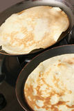 Cooking pancakes. Two frying-pans with pancakes Royalty Free Stock Photography