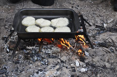 Cooking pancakes on a fire in field conditions. Stock Image