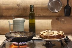 Cooking pancakes in a pan on the background of a log wall. Cooking pancakes on a frying pan against a log wall as a symbol of farm life royalty free stock image