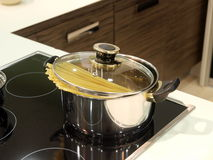 Cooking pasta. A pot with pasta cooking on the stove stock image