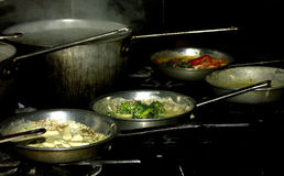 Cooking pasta. Various pasta sauces cooking with a pot of steaming water stock images