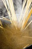 Cooking pasta. Spaghetti being cooked in hot water with steam making a dramatic image Stock Photo