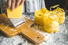 Cooking pasta by chef in kitchen on dark background Royalty Free Stock Photography