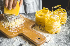 Cooking pasta by chef in kitchen on dark background Stock Photos