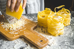 Cooking pasta by chef in kitchen on dark background Royalty Free Stock Images