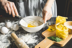 Cooking pasta by chef in kitchen on dark background Royalty Free Stock Photos