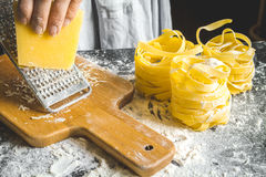 Cooking pasta by chef in kitchen on dark background Stock Image