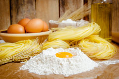 Cooking pasta concept. Eggs, flour, noodles, ears of wheat. Wooden background. Selective focus Royalty Free Stock Images