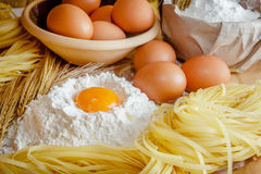 Cooking pasta concept. Eggs, flour, noodles, ears of wheat. Wooden background. Selective focus Stock Photography