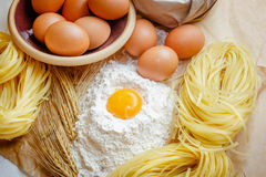 Cooking pasta concept. Eggs, flour, noodles, ears of wheat. Wooden background. Selective focus Stock Photos