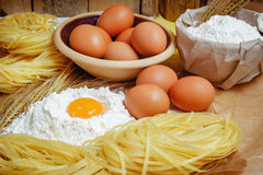 Cooking pasta concept. Eggs, flour, noodles, ears of wheat. Wooden background. Selective focus Stock Images