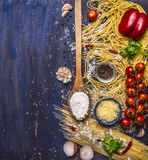 Cooking pasta concept with tomatoes, parmesan cheese, pepper, spices, flour, garlic, wooden spoon, border,  text area on blue Stock Images