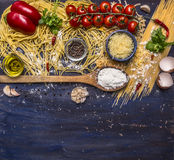 Cooking pasta concept with tomatoes, parmesan cheese, pepper, spices, flour, garlic, wooden spoon, border, with text area on blue Royalty Free Stock Photos