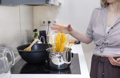 Cooking pasta, the girl throws the spaghetti in the pan to cook. Cooking pasta at home kitchen, the girl throws the spaghetti in the pan to cook spaghetti Stock Image