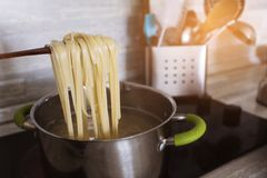 Cooking pasta at home in a pan. Spaghetti.  royalty free stock image