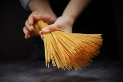 Hand made spaghetti in female hands against a dark background stock image