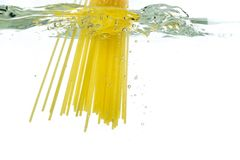 Cooking pasta spaghetti falling into boiling water and splash on white background.  stock image