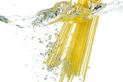 Cooking pasta spaghetti falling into boiling water and splash on white background.  stock photography