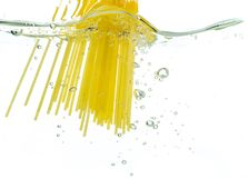 Cooking pasta spaghetti falling into boiling water and splash on white background.  royalty free stock photography