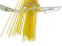 Cooking pasta spaghetti falling into boiling water and splash on white background.  royalty free stock image