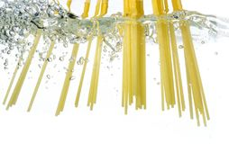 Cooking pasta spaghetti falling into boiling water and splash on white background.  stock photo