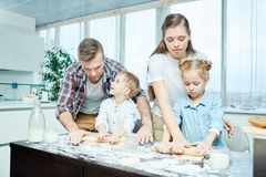 Cooking pastry. Father, mother, daughter and son rolling dough for homemade pastry on table Royalty Free Stock Photo