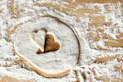 Cooking pastry for the holiday. Blank heart shape of farinaceous dough on a wooden table Stock Photo
