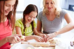 Cooking pastry. Portrait of happy girls and their mother cooking pastry in the kitchen Royalty Free Stock Photo