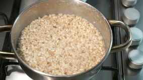 Cooking pearl-barley porridge on the gas stove stock video