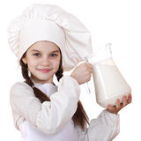 Cooking and people concept - Little girl in a white apron holdin Royalty Free Stock Photo