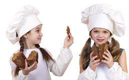 Cooking and people concept - Two little girls in cook hat Royalty Free Stock Photos
