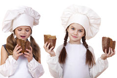 Cooking and people concept - Two little girls in cook hat Stock Photo