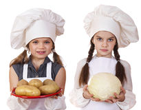 Cooking and people concept - Two Little girls in a white apron Royalty Free Stock Photo