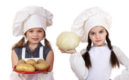 Cooking and people concept - Two Little girls in a white apron Royalty Free Stock Photos