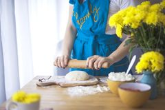 Cooking pie. cozy home. the woman is working with the test, on the table lies a rolling pin and flour. stock photo