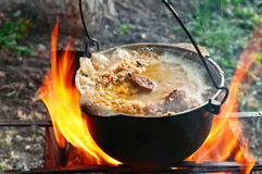 Cooking pilaf in a casserole on the fire close up Stock Images