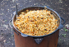 Cooking pilaf in a cauldron outdoors Royalty Free Stock Photos