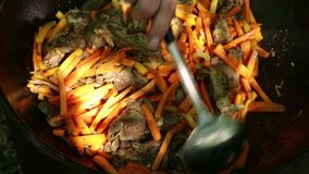 Cooking of pilaf. Grilled vegetables in a cauldron, outdoor. bbq food. camping concept.  stock video footage