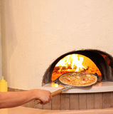 Cooking pizza. Putting pizza into hot oven Stock Images