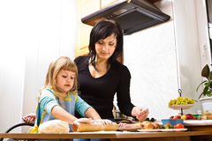 Cooking pizza. Mother teaching her little daughter how to cook pizza Stock Photos