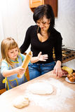 Cooking pizza. Mother teaching her little daughter how to cook pizza Stock Photography