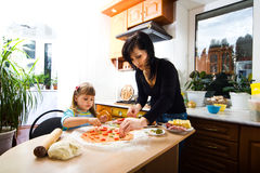 Cooking pizza. Mother teaching her little daughter how to cook pizza Stock Photo