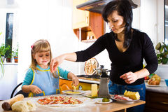 Cooking pizza. Mother teaching her little daughter how to cook pizza Royalty Free Stock Images