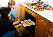 Cooking pizza. Mother teaching her little daughter how to cook pizza Stock Image