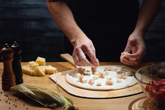 Cooking pizza. Chef cooking pizza, putting topping on pizza base. Low key shot, close up of hands, some ingredients around on table stock image