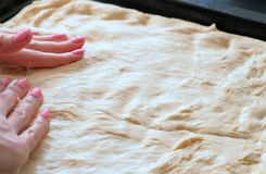Cooking pizza. Closeup woman`s hands lays out the dough on a baking sheet, spreading all over the baking sheet pan. stock photo